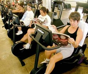 reading-newspaper-while-riding-stationary-bikes